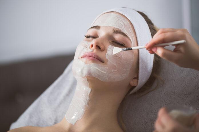 Kobieta podczas nakładania peelingu chemicznego na twarz