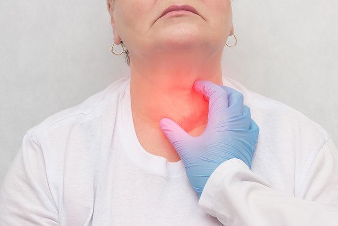 Niedoczynność tarczycy - lekarz badający tarczycę kobiety.